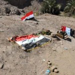 epa04694539 Iraqi flag covers the site believed to be a mass grave of suspected Islamic State (IS) massacre victims, at Speicher base in Tikrit, northern Iraq, 07 April 2015. Iraqi security forces said that since recapturing the city of Tikrit last week they had found 14 mass graves, containing bodies including those of soldiers captured by the militants after fleeing from Speicher military base. The Sunni jihadist group claimed at the time to have executed 1,700 Shiite soldiers who had surrendered to it after fleeing the nearby Camp Speicher.  EPA/STR