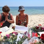 epaselect epa04822452 A Tourist prays beside flowers placed in tribute to the people killed in a terror attack on a beach in front of the imperial Marhaba Hotel in Sousse,Tunisia, 28 June 2015. According to local reports 26 June, an assailant with handgrenades opened fire on tourists at two hotels, killing at least 37 people, including Germans, Brits and Belgians, and wounding several others, some while they were sunbathing, the attacker was killed later in a gun fight with Tunisian security services, while people beleieved to be associated with him have since been arrested in the country. The group which calls itself the Islamic State (IS) have claimed responsibility.  EPA/MOHAMED MESSARA