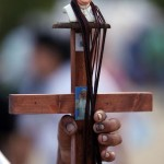 A street vendor sells a crucifix with the image of Pope Francis, at the Samanes Park where the Pope will give a mass in Guayaquil, Ecuador, Sunday, July 5, 2015. Francis is making his first visit as pope to his Spanish-speaking neighborhood. He'll travel to three South American nations, Ecuador, Bolivia and Paraguay, which are beset by problems that concern him deeply, income inequality and environmental degradation. (ANSA/AP Photo/Fernando Vergara)