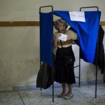 A woman holds her ballot paper before casting it at a polling station in Athens, Sunday, July 5, 2015. Greeks began voting early Sunday in a closely-watched, closely-contested referendum, which the government pits as a choice over whether to defy the country's creditors and push for better repayment terms or essentially accept their terms, but which the opposition and many of the creditors paint as a choice between staying in the euro or leaving it. (ANSA/AP Photo/Emilio Morenatti)