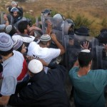epa04863337 Israeli security forces scuffle with Israeli settlers who refuse to leave during the evacuation of a 24 housing units illegal building site where settlers had barricaded at the Jewish settlement of Beit El, near the West Bank town of Ramallah, early 28 July 2015. Israel's Supreme Court earlier had ruled to demolish the 24 housing units in the settlement claiming  they were illegally built on private Palestinian land.  EPA/ABIR SULTAN