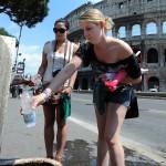 Due turiste riempiono una bottiglietta d'acqua da una fontanella oggi al Colosseo a Roma. ANSA/CLAUDIO ONORATI/on