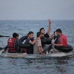 Migrants who tried to cross to the nearby Greek island of Kos,  from near the coastal town of Bodrum, Turkey, early Tuesday, Aug. 18, 2015 , wave as they approach the shore after their failed attempt. The people said they were paddling for nearly 3 hours until they gave up and return. Five people have drowned off the Turkish coast as they tried to reach the Greek islands, underscoring the deadly risks of overcrowded plastic dinghies making even short crossings to Europe by people fleeing conflict in the Middle East and Africa. (ANSA/AP Photo/Lefteris Pitarakis)