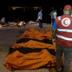 In this Thursday, Aug. 27, 2015 photo, rescuers gather around the bodies of drowned migrants in Zuwara, Libya. (ANSA/AP Photo/Mohamed Ben Khalifa)
