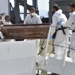 Personnel disembarks a coffin from Italian Coast Guard ship Diciotti at the Messina harbor in Sicily, Italy, Saturday, Aug. 29, 2015. Migrants by the tens of thousands are braving the perilous journey across the Mediterranean, fleeing war and poverty in the Middle East, Africa and Asia with the hope of reaching Europe and be granted asylum. (ANSA/AP Photo/Carmelo Imbesi)