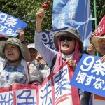 epa04847309 Demonstrators protest against a controversial security bill outside Japan's parliament in Tokyo, Japan, 15 July 2015, after the bill was passed during a parliamentary committee. Reports state that, despite large public opposition, the ruling coalition led by Prime Minister Abe pushed through security bills at a committee session in order to pass the new law to the lower house on 16 July to enable expansion of the role of Japan's military forces overseas. Opponents argued that Abe's initiative for the military could go against Japan's post-war constitution. Article 9 of the charter prohibits the use of force to settle international disputes. The blue placard reads 'Don't break Article 9 of the Constitution'.  EPA/KIMIMASA MAYAMA