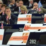 epa04967461 During the speech of German Chancellor Angela Merkel, far-right Members of Parliament protest with placards in the European Parliament in Strasbourg, France, 07 October 2015. The Middle East is at the risk of 'all-out war' if its religious confrontations are left unchecked, French President Francois Hollande warns during a joint address to the European Parliament with German Chancellor Angela Merkel.  EPA/PATRICK SEEGER