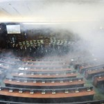 epa05049361 Opposition lawmakers throw tear gas during a session of Kosovo's parliament in Pristina, Kosovo, 30 November 2015. Opposition lawmakers used tear gas at the start of the parliament session to protest against the agreements that Kosovo's government reached during the EU-brokered dialogue with Serbia.  EPA/PETRIT PRENAJ