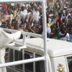 Pope Francis waves to the crowd as he arrives with the popemobile on the occasion of his visit at the Central Mosque in Bangui's Muslim enclave of PK5, Central African Republic, Monday Nov. 30, 2015. The Pope was welcomed by a crowd of people and prayed inside the Central Mosque. (ANSA/AP Photo/Jerome Delay)