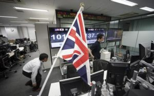 Money traders walk past a flag of the United Kingdom at a foreign exchange brokerage at a securities firm in Tokyo, Friday, June 24, 2016. Global financial markets fluctuated on Friday as votes are tallied in the referendum deciding if Britain is to leave the European Union. (ANSA/AP Photo/Eugene Hoshiko) [CopyrightNotice: Copyright 2016 The Associated Press. All rights reserved. This material may not be published, broadcast, rewritten or redistribu]