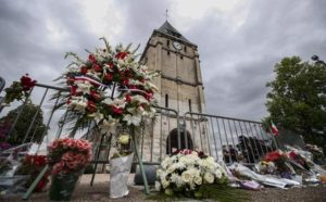 epaselect epa05444192 People pay tribute at a makeshift memorial near the Saint Etienne church, where priest Jacques Hamel was killed, in Saint-Etienne-du-Rouvray, near Rouen, France, 27 July 2016. According to reports, two hostage takers were killed by the police after they took hostages at a church in Saint-Etienne-du-Rouvray. One of the hostages, a priest was killed by one of the perpetrators.  EPA/IAN LANGSDON